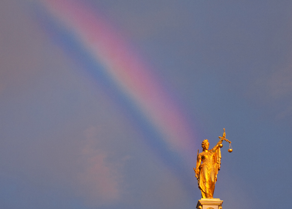 Justitia on rooftop with rainbow behind. Taken in Bruges, Belgium.