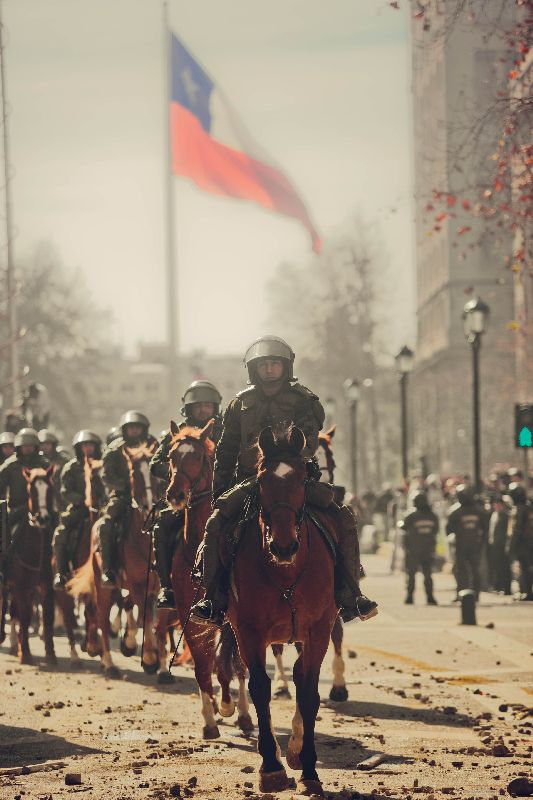 policemen on horses while riots in Santiago de Chile, 2011