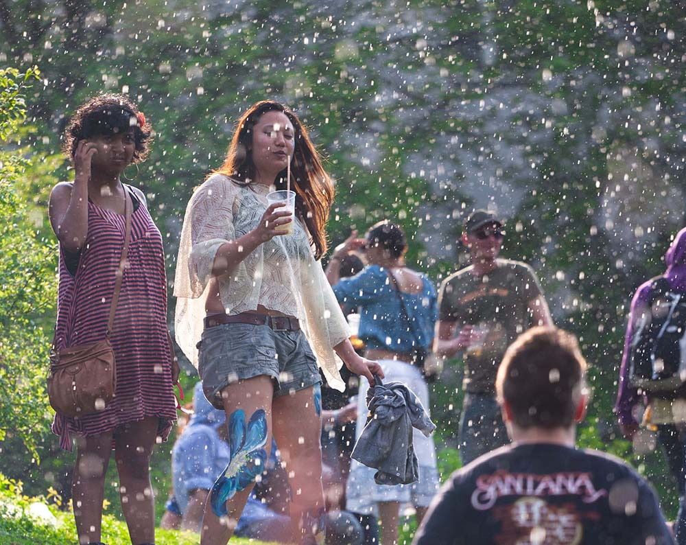 People enjoying a short shower of rain while the sun is still shining in Görlitzer Park at Mayfest on May 1st 2012 in Berlin