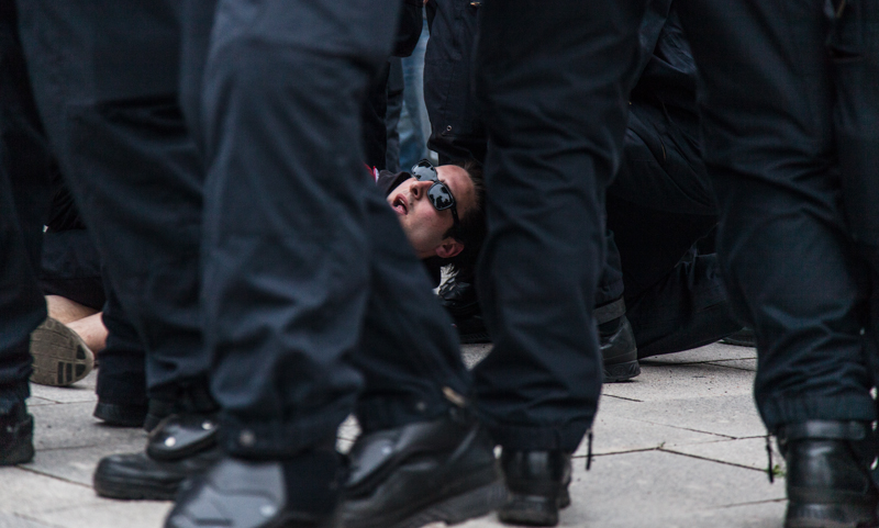 Arrested demonstrator surrounded by police