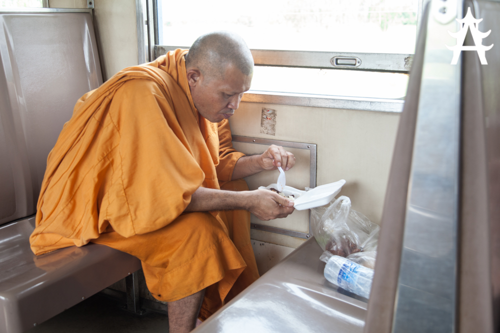 Monk eating his lunch that was given as a donation